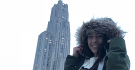 Christen Stefanelli in a winter coat in front of the Cathedral of Learning